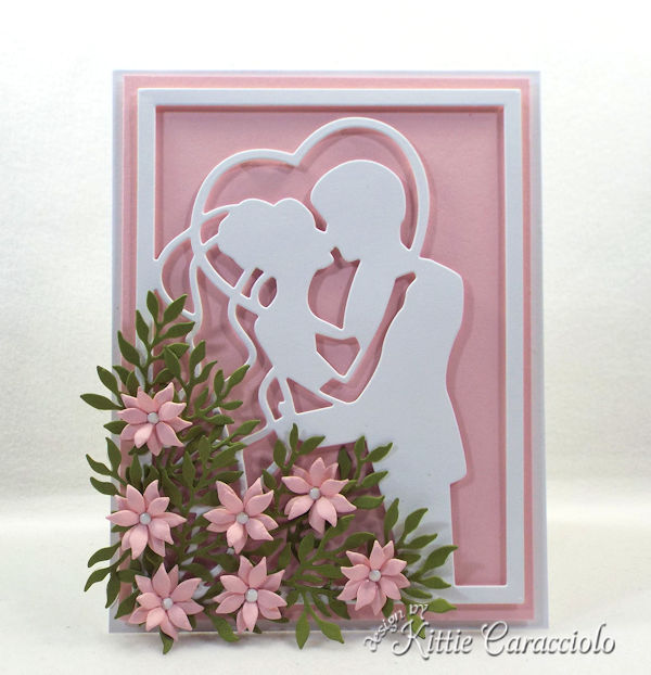 You can create an elegant framed wedding card using die cut paper flowers.