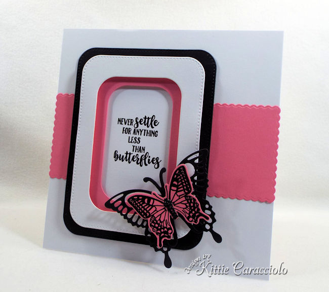 A pink and black die cut butterfly is pretty on a clean and simple background.