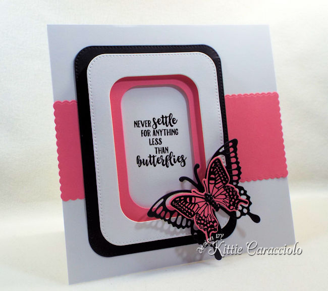 A pink and black die cut butterfly is pretty on a simple white background.
