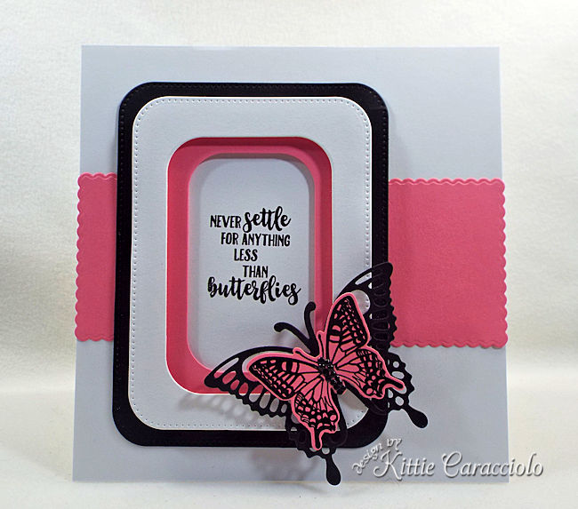 A pink and black die cut butterfly is pretty on a white clean and simple background.