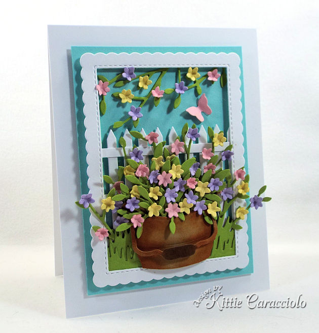 Come see how I made this die cut fence and bucket scene card perfect for anyone who loves flowers.