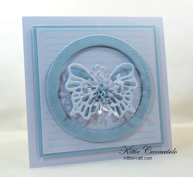 Come see how I made this elegant circle framed die cut butterfly card with a French script background and tiny flowers.