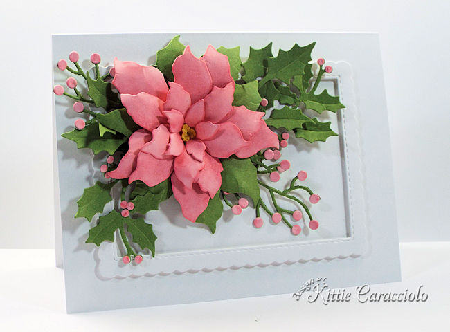 Come see how I made this beautiful die cut pink poinsettia embellished with holly and berry branches.