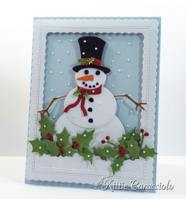 Come see how I made this die cut snowman scene with falling snow and holly.