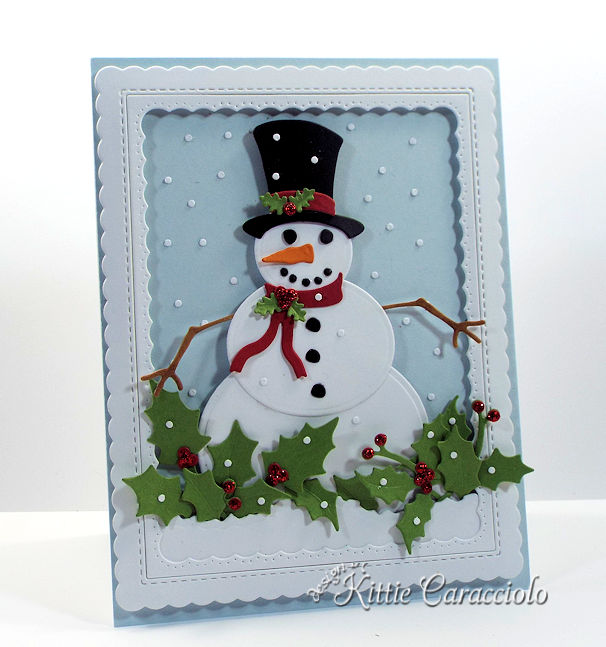 Come see how I made this festive die cut snowman scene with falling snow and holly.