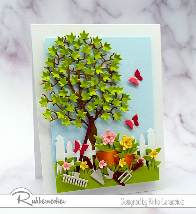 KC Rubbernecker 5309-07D Garden Tools 1 leftIt was so much fun to create this garden tools dies card with the colorful flower pots and leafy tree. Click thru to see how I created this cheerful scene.