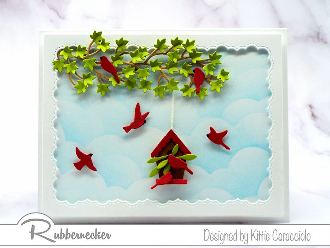 Come over to see how I made this framed birds and birdhouse card with the pretty blue sky background using dies made by Rubbernecker.