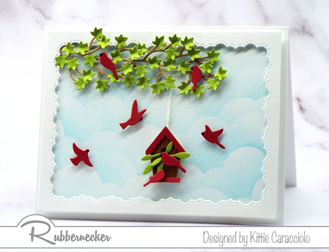 Come see how I made this framed birds and birdhouse card with the pretty blue sky background using dies made by Rubbernecker.