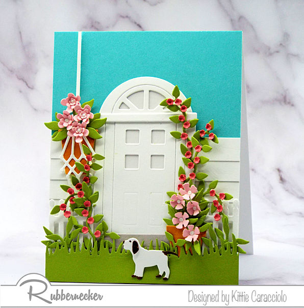 Door cards have become very popular in paper crafting. Embellishing the door with flowers and foliage creates a pretty welcoming scene.