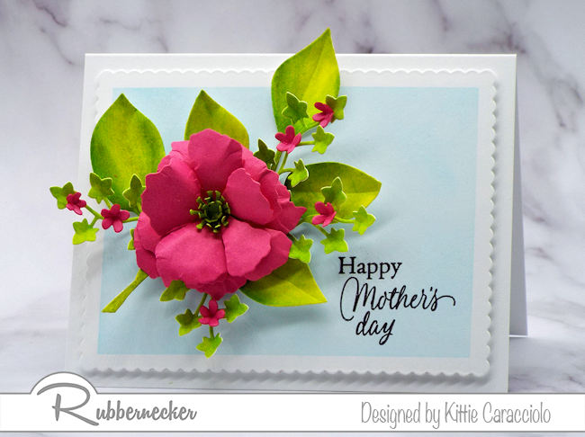 Bright, colorful flowers and foliage are the perfect embellishment on a happy Mother's Day card. Come see how I made this using dies by Rubbernecker Stamps.
