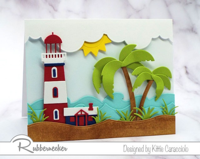 A handmade card of a lighthouse and palm tree on a beach demonstrating how altering die cuts can help them fit different sized projects
