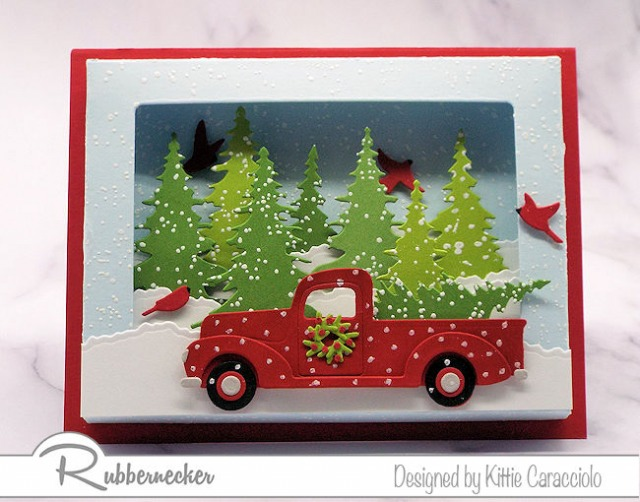 Die cut pine trees and a classic red pickup truck are all arranged in an adorable scene made using a shadow box card die