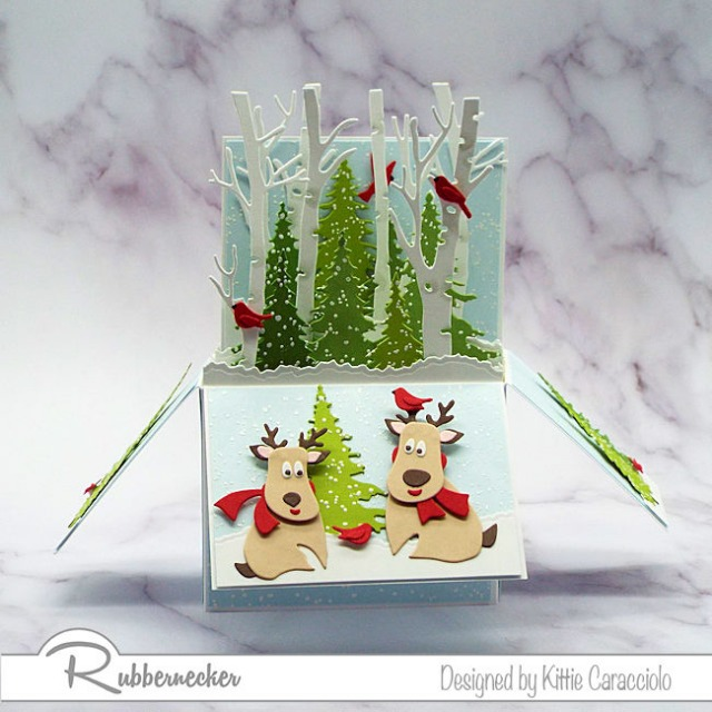 an adorable Christmas pop up card depicting two die cut reindeer frolicking in their snowy forest
