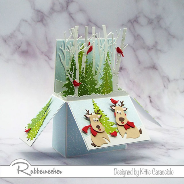 A handmade Christmas pop up card with adorable die cut reindeer playing in their snowy forest