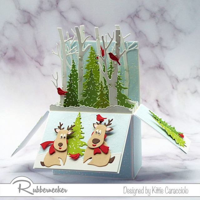 An adorable Christmas pop up card with two reindeer playing in the snowy forest.