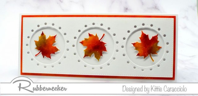 One of my fall card ideas shpwing hand colored and die cut maple leaves centered inside three circular die cut windows on a slimline card made using all Rubbernecker products