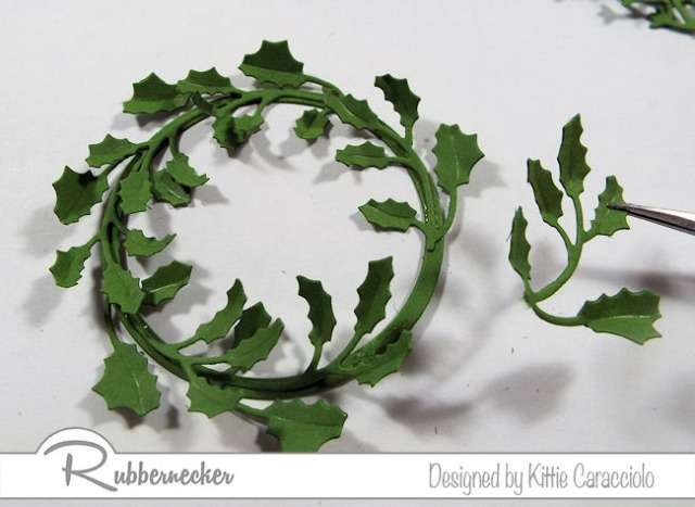 Learn how to make a wreath with die cuts as shown here with the first layer of die cut greenery being placed on a paper ring