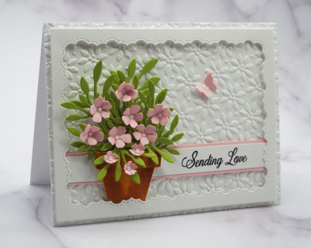 Using tiny paper flowers against an overall-embossed background gives them a ton of impact on your handmade cards