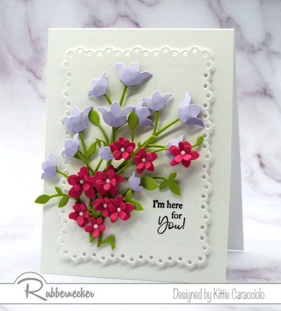 this white on white layered card with hot pink and soft purple flowers shows how to make paper flower card embellishments with die cuts