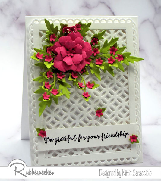 a card background design created by cutting card stock with a overall design die in white, layered on white, with a single flower made with dies, all from Rubbernecker