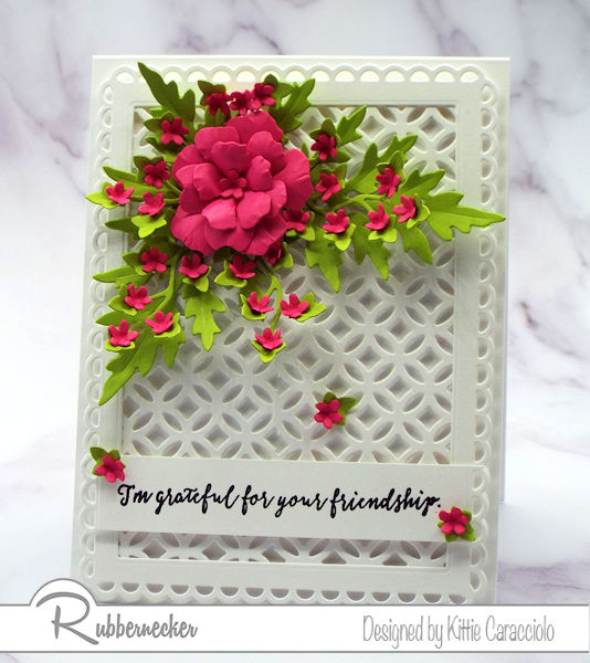 A beautiful card background design of a white on white overall die cut set with a 3D paper flower, all made with dies from Rubbernecker