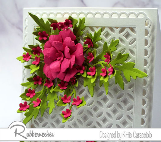 a white on white card background design made with dies from Rubbernecker decorated with a single paper flower made with a die set