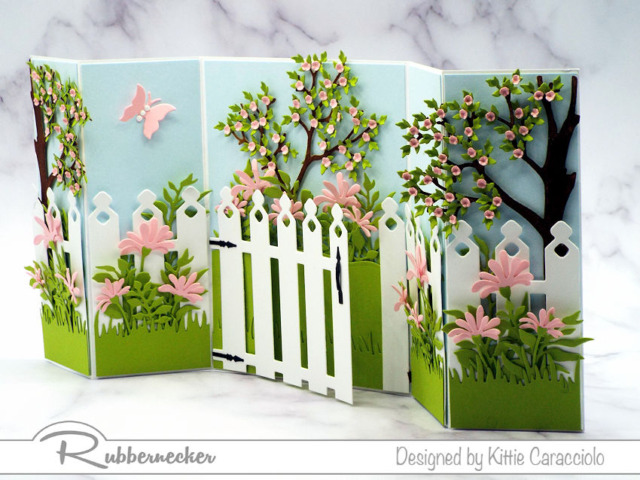 This shutter card design is LOADED with detail all made with dies from Kittie Kraft by Rubbernecker to create the garden gate, flowers and all the lush foliage