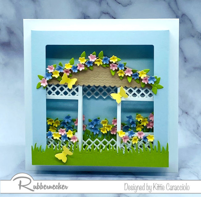 a floral gazebo card with a cute 3D paper gazebo tucked into a shadow box frame loaded with flowers all made using dies from Rubbernecker