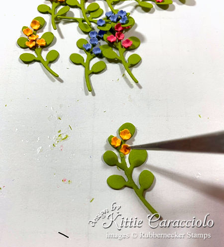 die cut leftovers being turned into tiny sprigs of flowers for use on a handmade greeting card