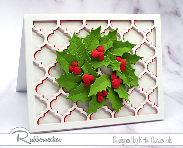 A mass of die cut holly leaves arranged in a wreath over die cut layers to create a beautiful handmade greeting card