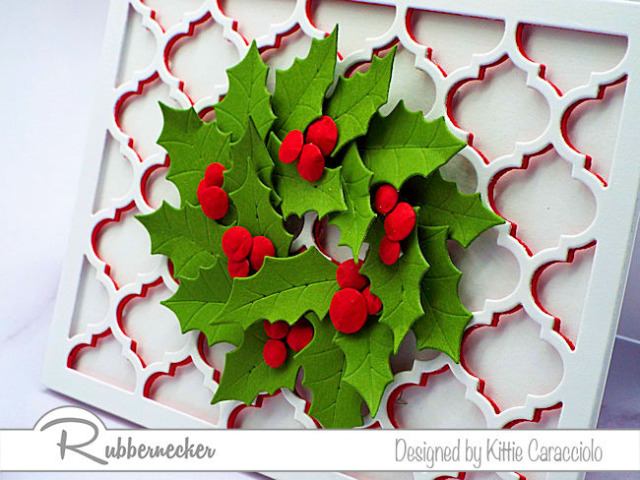 a handmade holiday greeting card made with die cut holly leaves and layered die cut backgrounds all from Rubbernecker