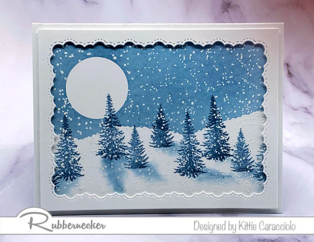 this hand stamped winter pine tree card in shades of deep blue and white is made using a new set of pine tree stamps from Rubbernecker